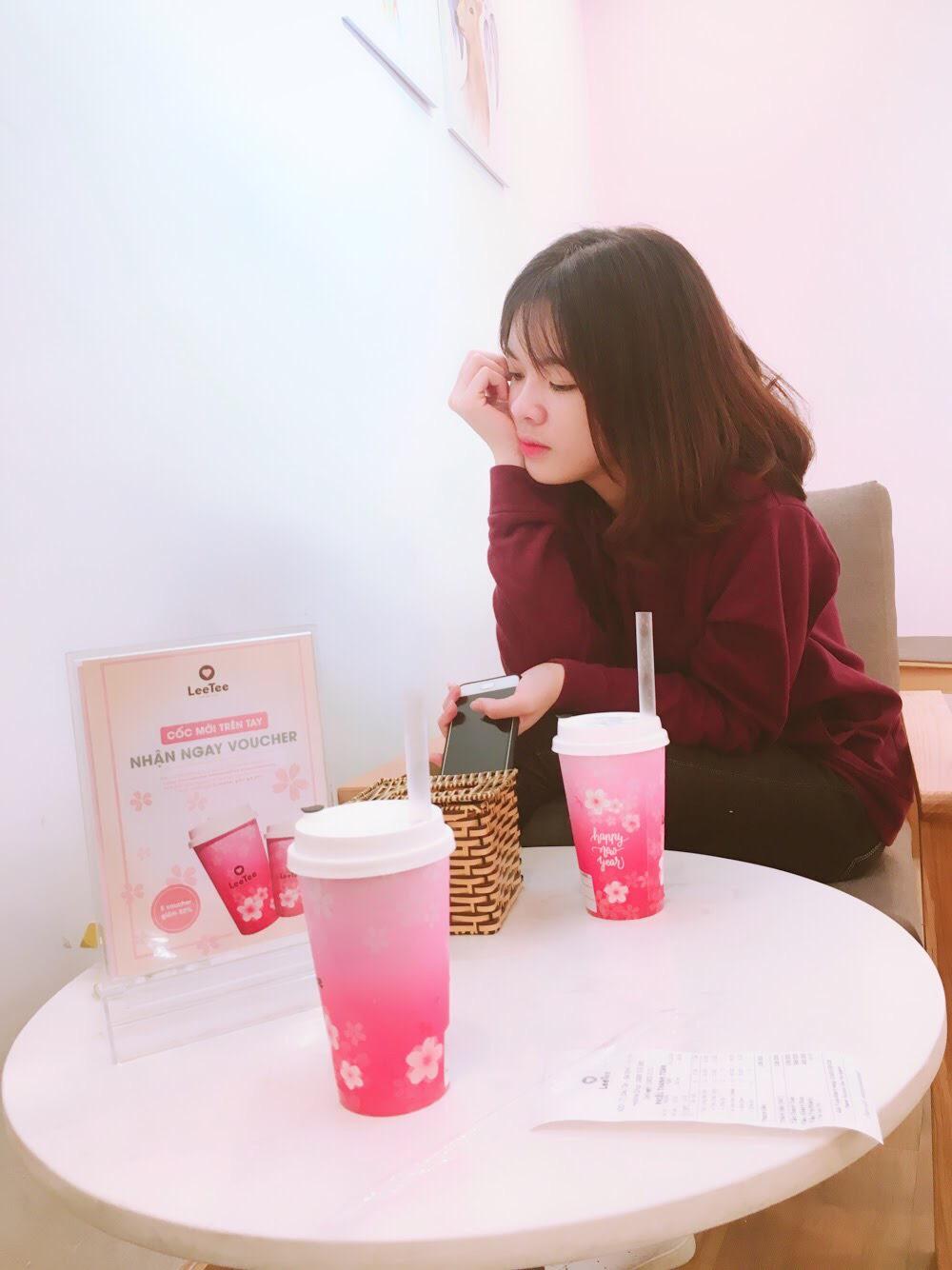 Cô gái ngồi bàn trà sữa